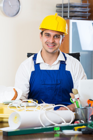 25 35: Successful engineer in uniform working with equipment at office Stock Photo