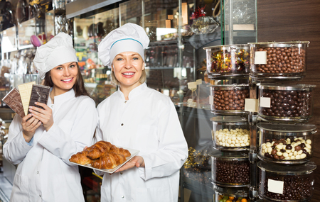 45 50: Smiling adult women selling fine chocolates and sweet pastry in coffee-house