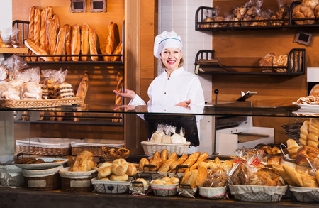 55 60: Aged bakery employee offering bread and different pastry for sale