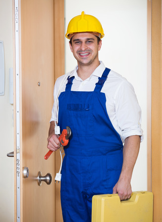 service man: Happy handyman in uniform with tooling at house entrance