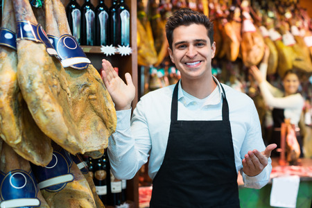 delicatessen: Worker selling Spanish jamon and smiling in delicatessen store