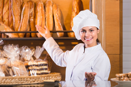 shopgirl: Happy shopgirl working in bakery with bread and different pastry indoor Stock Photo