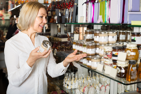honey blonde: Smiling mature blonde consumer buying jar with white honey in cafe