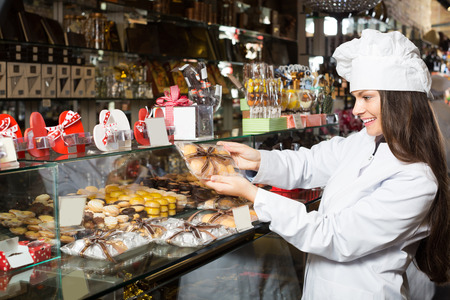 shopgirl: Young positive woman selling fine chocolates and confectionery in cafe Stock Photo