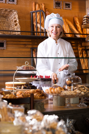 45 50: Pretty senior woman selling fresh pastry and baguettes in local bakery