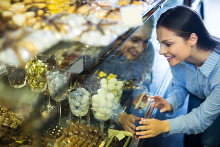 shopgirl: Smiling adult woman selecting fine chocolates and confectionery at cafe display
