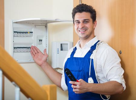 electric meter: manitas profesional cerca de medidor eléctrico en el interior doméstico Foto de archivo