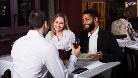 middle class: Happy middle class couple and friend enjoying food in cafe