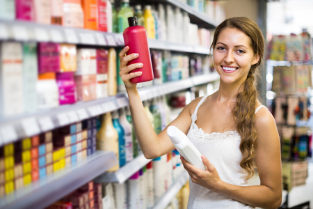 vend: Young happy  girl buying shampoo in shopping mall Stock Photo