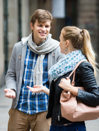 sidewalk talk: Girl in leather jacket flirting with handsome young guy at the street