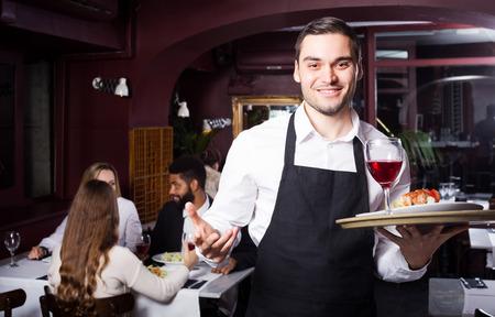 clase media: Retrato de los adultos en el restaurante de clase media y camarero adulto alegre Foto de archivo