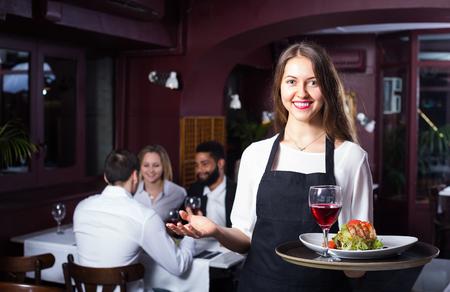 joven y atractiva que sirve comida camarera sonriente restaurante para los clientes en la mesa