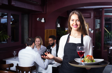 30 35: Smiling young attractive waitress serving meal for restaurant guests at table
