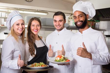 mandil: camarera positiva y equipo de cocina en la cocina profesional en restaurante Foto de archivo