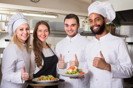 Positive waitress and cooking team at professional kitchen in restaurant