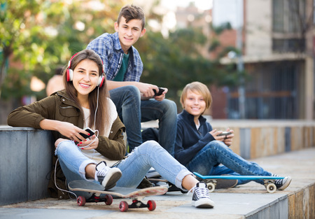 16s: Three teenagers with smartphones in autumn day outdoors Stock Photo