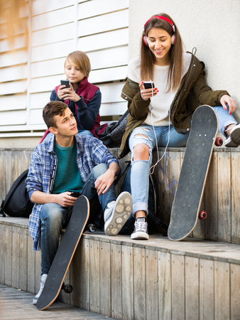 16s: Three caucasian teenagers with smartphones in autumn day outdoors