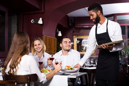 middle class: Portrait of adults in middle class restaurant and cheerful waiter Stock Photo
