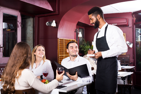 middle class: Portrait of young people in middle class restaurant and black waiter