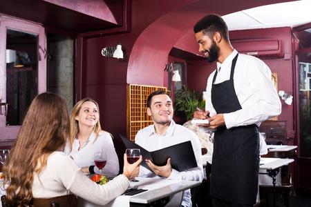 middle class: Retrato de los jóvenes en el restaurante de clase media y el camarero negro