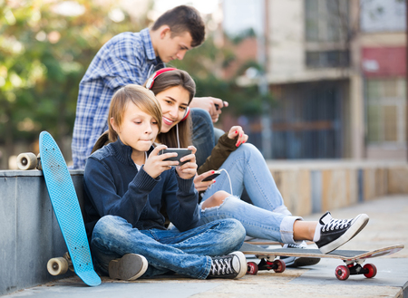 16s: Three happy american teenagers with smartphones in autumn day outdoors Stock Photo