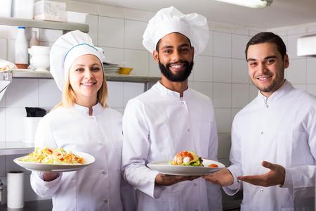 kitchen spanish: Crew of positive spanish professional cooks working at restaurant kitchen