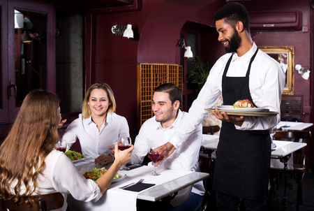 middle class: Portrait of adults in middle class restaurant and cheerful black waiter Stock Photo