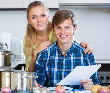 middle joint: Family couple filling forms for joint banking account at kitchen Stock Photo
