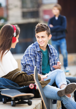 'teenager boy: Envy male teen standing aside of girlfriend talking with boy outdoors