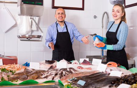 shopgirl: Shopgirl and salesman posing near display with nutrition chilled fish