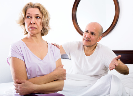 scandals: Adult man and sadness woman getting through scandals and blamings in bedroom