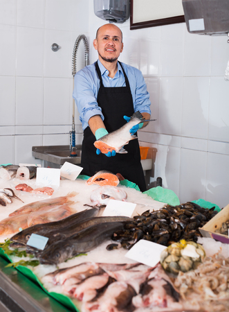 45 50: Cheerful mature salesman with apron offering fresh fish in shop