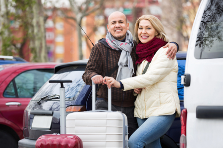 a two wheeled vehicle: Senior couple of travellers posing with trollers near parked car Stock Photo