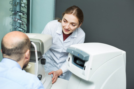 55 60: Young friendly positive female optician doing eye examination with aid of slit lamp Stock Photo