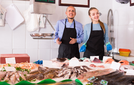 shopgirl: european shopgirl and salesman posing near display with chilled fish Stock Photo