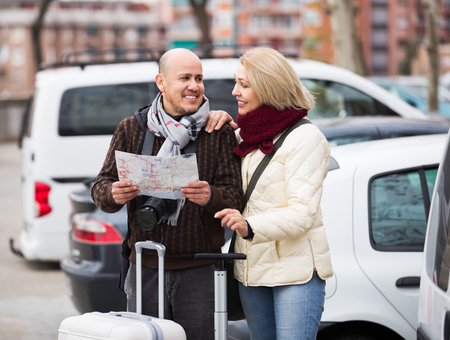 a two wheeled vehicle: Portrait of elderly spouses with baggage and paper map outdoors