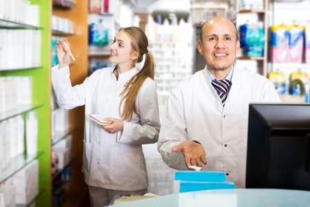 farmacy: Adult pharmacist and assistant working at farmacy reception