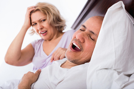 snoring: Mature  angry girlfriend cannot stand guy snoring loudly in sleep Stock Photo