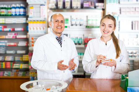 farmacy: Experienced pharmacist and assistant working at farmacy reception