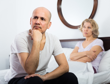 sorting out: Sad elderly man and frustrated mature woman sorting out relationships in bed