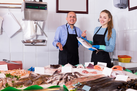 shopgirl: Shopgirl and salesman posing near display with chilled fish in fishery shop