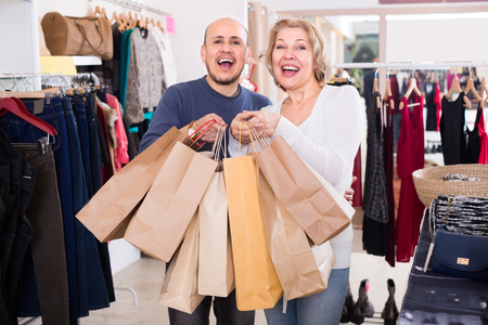 wife and husband carrying bags with purchases in clothing store Stock Photo - 53913950