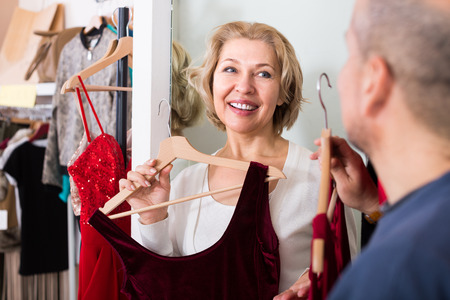 fitting in: Portrait of smiling mature couple trying on new dress in fitting room at boutique