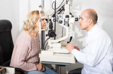 slit: american mature optician examinating eyesight with aid of slit lamp Stock Photo