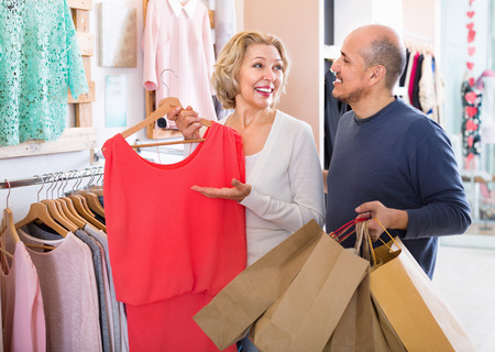 spanish woman: Glad senior husband helping charming wife to select dress at apparel store