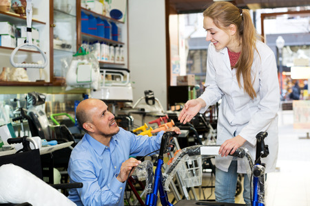 orthopaedic: Attractive female consultant offering wheelchair to mature customer in orthopaedic store. Focus on the woman Stock Photo