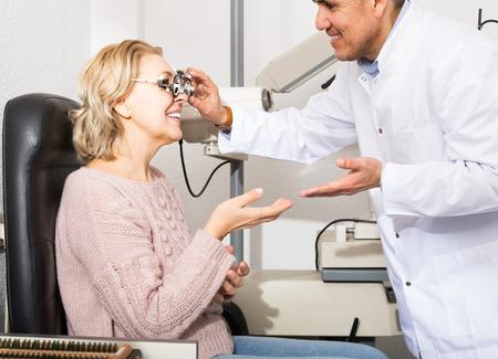 slit: smiling mature optician examinating eyesight with aid of slit lamp
