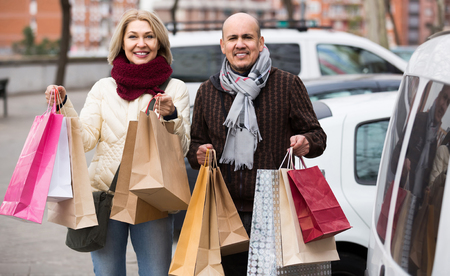 55 60: spanish elderly couple carrying purchases and smiling outdoors