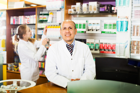 farmacy: Portrait of elderly pharmacist and young assistant working at farmacy reception
