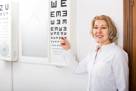 45 50: Elderly optician showing symbols of Snellen chart in modern clinic